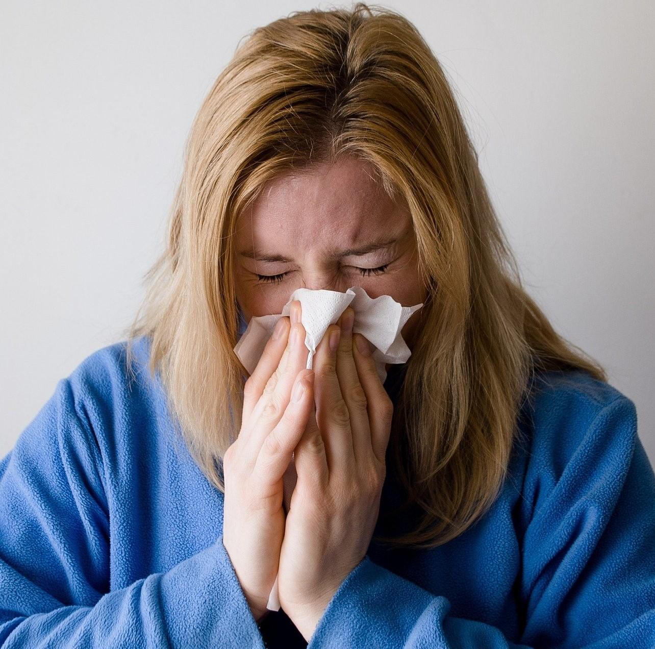 femme éternuant à cause d'une allergie aux acariens